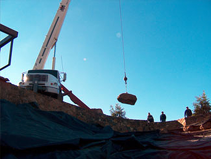 crane lifting large rock into place
