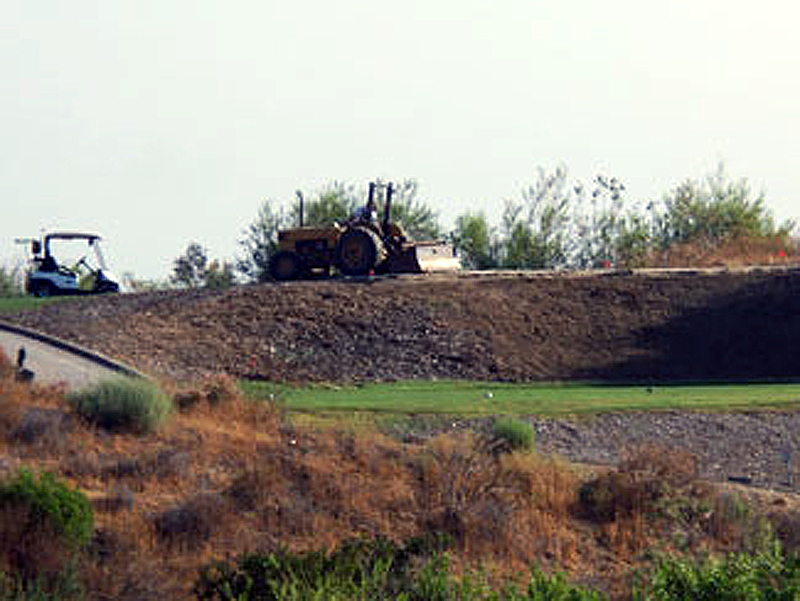golf course repair with men and heavy equipment